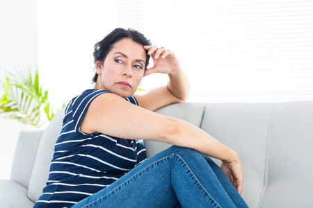 dreariness: Unhappy woman sitting on the couch on white background Stock Photo