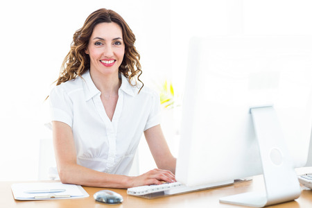 fashionable female: Smiling businesswoman working with computer on white background