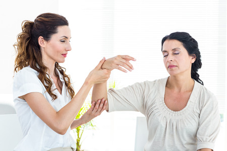hypnosis: Therapist holding her patients arm on white background