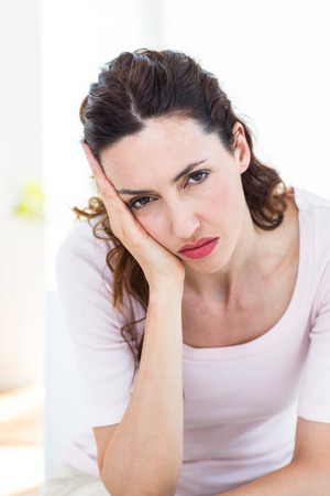 solitariness: Upset brunette sitting on the couch on white background