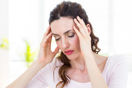 dolor de cabeza: Morena tiene dolor de cabeza en el fondo blanco