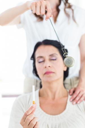 Woman being hypnotized to quit smoking on white background Zdjęcie Seryjne
