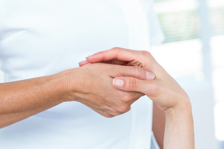 Physiotherapist examining her patients hand in medical office Stock Photo