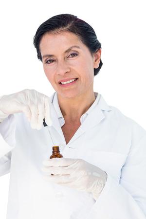 Confident female doctor holding medicine bottle on white background photo