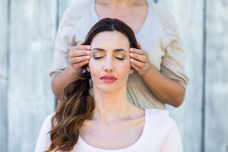 Woman getting reiki therapy on wooden background