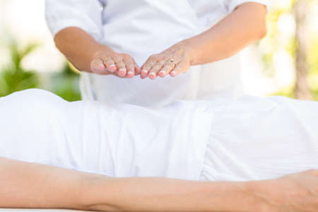 on hands: Calm woman receiving reiki treatment in the health spa Stock Photo