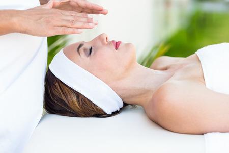 reiki: Calm woman receiving reiki treatment in the health spa Stock Photo