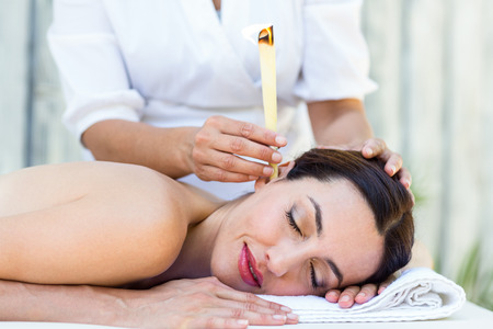 by ear: Relaxed brunette getting an ear candling treatment at the spa