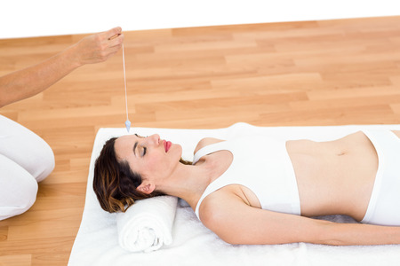 hypnotherapy: Woman being hypnotized while lying on the floor on white background