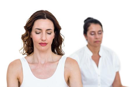 mujeres maduras: Mujeres que se sientan en posici�n de loto en el fondo blanco Foto de archivo
