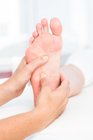 Physiotherapist massaging her patients foot in medical office Stock Photo