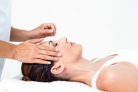 spa treatments: Relaxed woman receiving an acupuncture treatment in a health spa