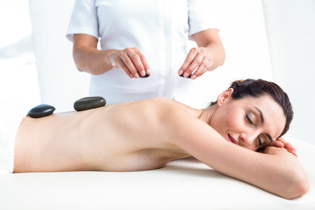 hot stone: Smiling brunette getting hot stone massage in a healthy spa