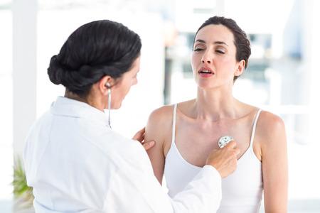 persona respirando: Doctor que escucha a los pacientes en el pecho con un estetoscopio en el consultorio médico