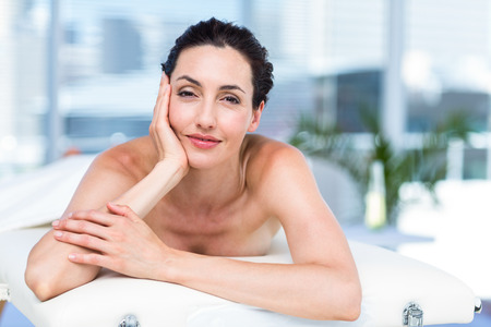 massage  table: Smiling brunette relaxing on massage table in a healthy spa Stock Photo