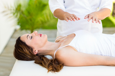 heal: Calm woman receiving reiki treatment in the health spa Stock Photo
