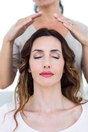 reiki: Woman getting reiki therapy on white background Stock Photo