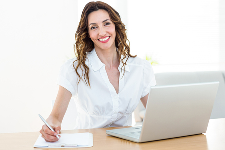 Smiling businesswoman working with her laptop and taking notes on white background Stock Photo
