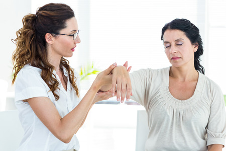 hypnotherapy: Therapist holding her patients arm on white background