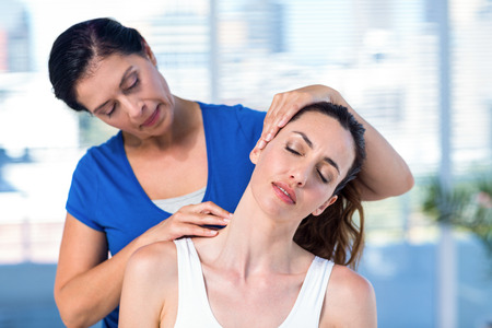 physiotherapy: Therapist examining her patients neck in exercise room