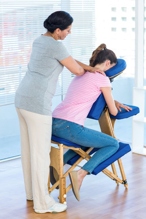 massage chair: Woman having shoulders massage in medical office