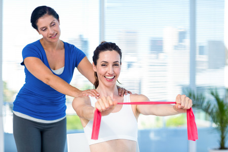 slender woman: Brunette stretching with her coach and pink cloth in exercise room Stock Photo