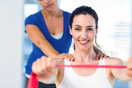exercise room: Brunette stretching with her coach and pink cloth in exercise room Stock Photo