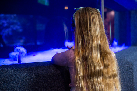 sea anemone: Woman looking at sea anemone in tank at the aquarium