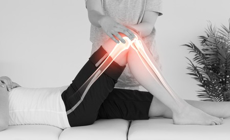 knee: Digital composite of Highlighted bones of woman at physiotherapist Stock Photo