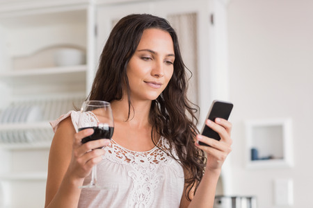 Pretty brunette using smartphone and having glass of wine in the kitchen photo