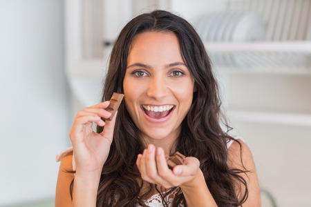 munching: Happy pretty brunette eating chocolate in the kitchen