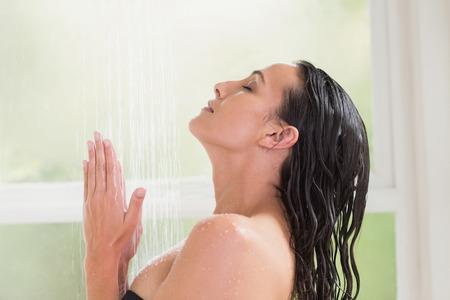 Pretty brunette taking a shower in a bathroom photo