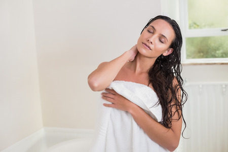 after the bath: Pretty brunette holding her bath towel after shower