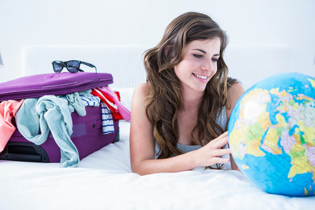 Woman with a suitcase and globe while lying on her bed at home in the bedroom photo