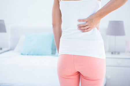 pain: Woman with back pain at home in the bedroom