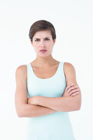 outraged: Angry woman looking at camera with arms crossed on white background