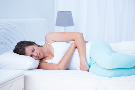 lying on the stomach: Pretty woman with stomach pain at home in the bedroom