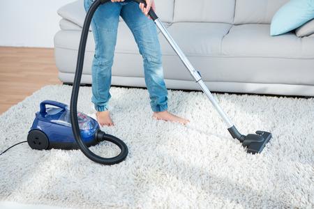 거실에서 카펫에 진공 청소기를 사용하는 여자
