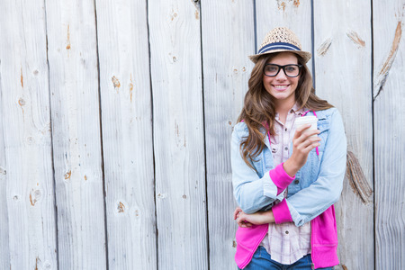 hot drink: Cute woman holding disposable cup coffee against wooden planks