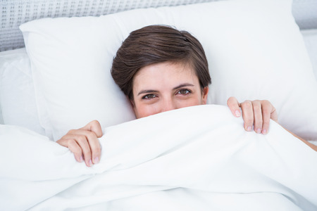 Beautiful woman smiling under the duvet at home in the bedroom