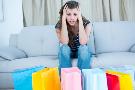regretful: Regretful woman looking at many shopping bags at home in the living room Stock Photo