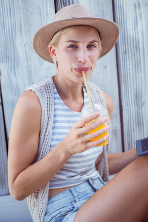 Pretty blonde woman using her tablet and drinking orange juice on wooden background photo