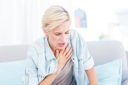 atmung: Pretty blonde Frau mit Atemschwierigkeiten im Wohnzimmer Lizenzfreie Bilder