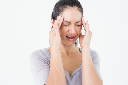 wincing: Brunette suffering from migraine on white background