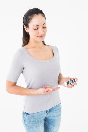 blood glucose: Diabetic brunette holding blood glucose monitor on white background