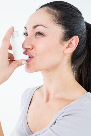 asthmatic: Asthmatic pretty brunette using inhaler on white background