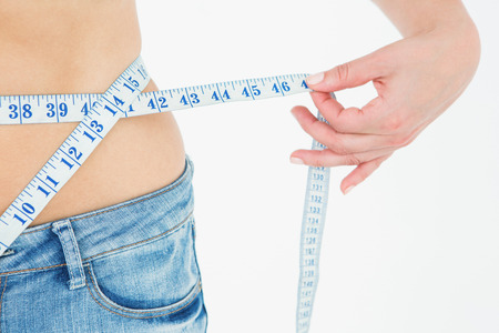 Woman measuring her waist on white background