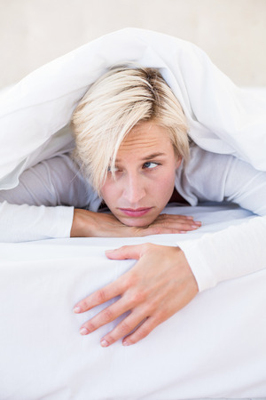 dreariness: Sad blonde woman lying on the bed in her bedroom