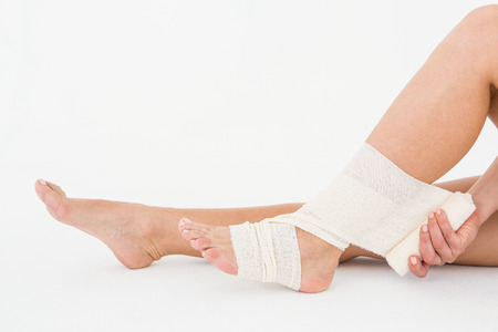 achilles tendon: Sitting woman banding her ankle on white background