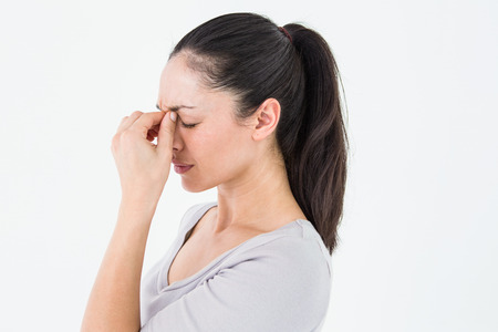 pounding head: Brunette suffering from migraine on white background